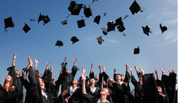 Graduating students tossing caps into the air