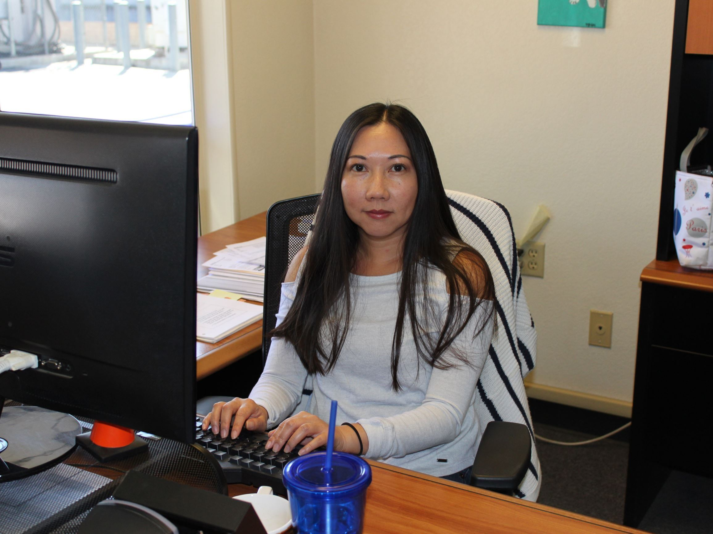 Female staff member sits behind at desk behind a computer.